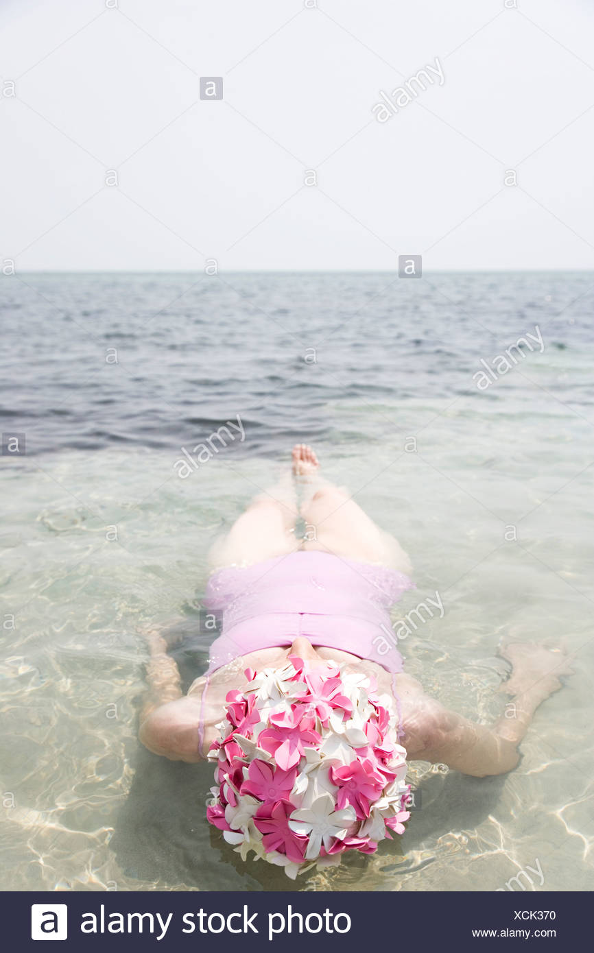 Senior woman in a swimming hat, swimming in the ocean - Stock Image