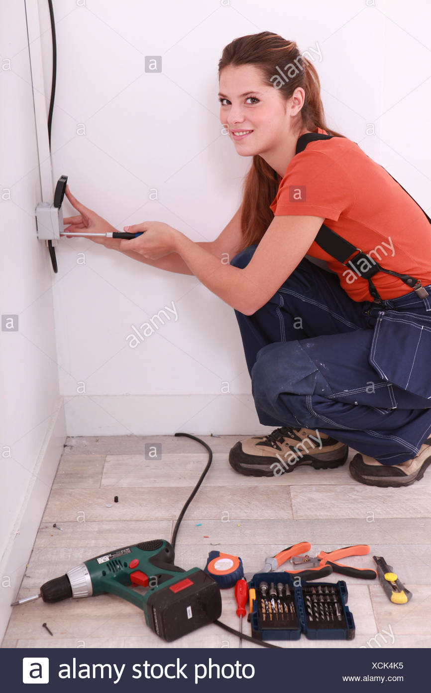 young woman screwing an electrical outlet - Stock Image