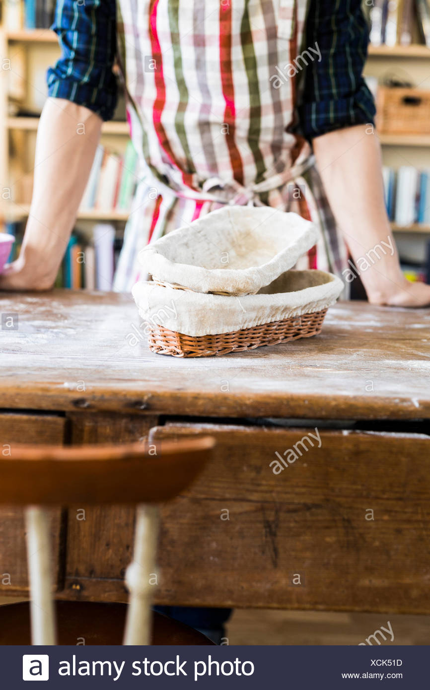 Midsection of baker with baskets in bakery - Stock Image