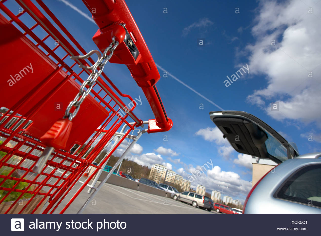 Tilt shot of red trolley and cropped car below blue sky and clouds - Stock Image