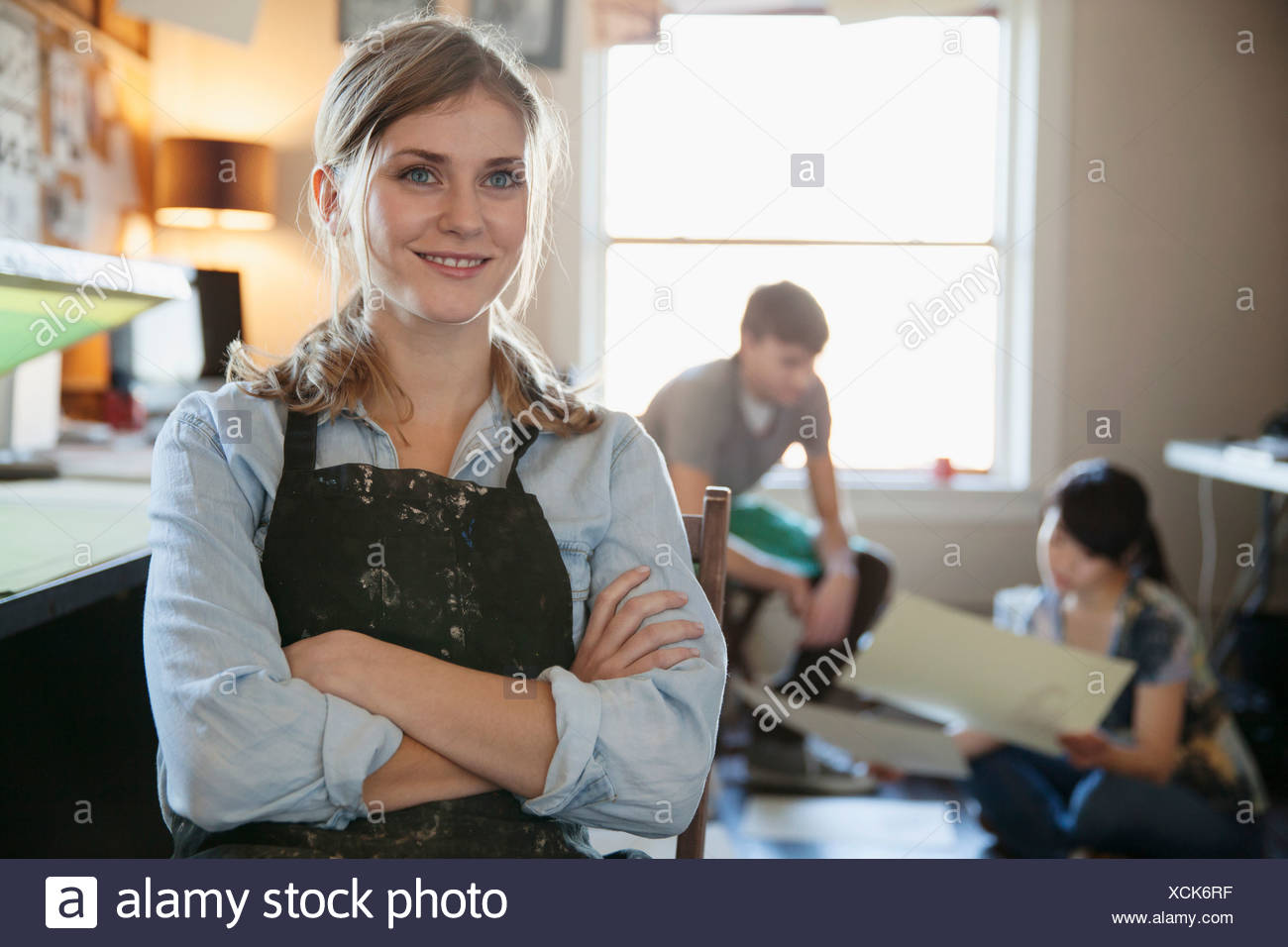 Confident female design professional looking away with colleagues in background at workshop - Stock Image