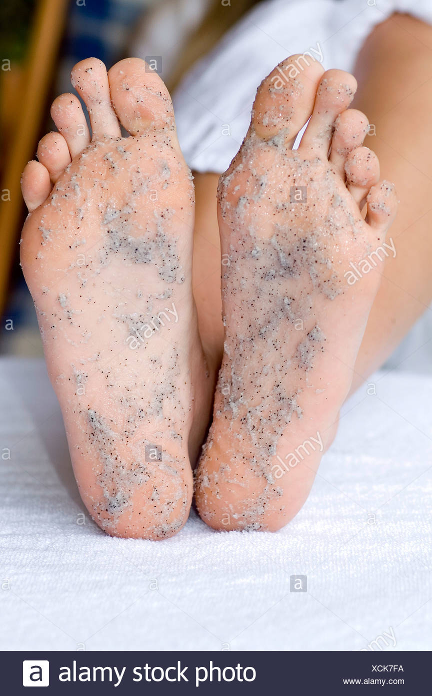 Female with grey foot scrub on soles of feet - Stock Image