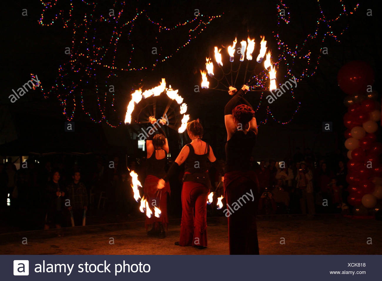 Fire dancing troupe performing at an outdoor nighttime celebration - Stock Image