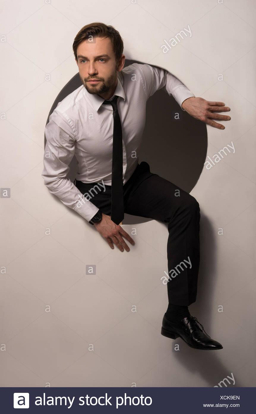 Businessman Climbing Out Of A Circular Hole