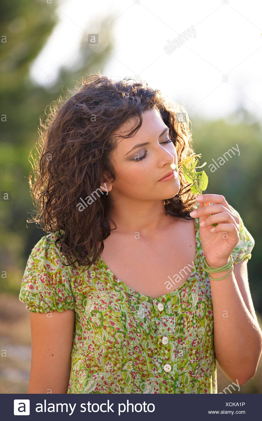 Woman breathing the odor of a plant - Stock Image