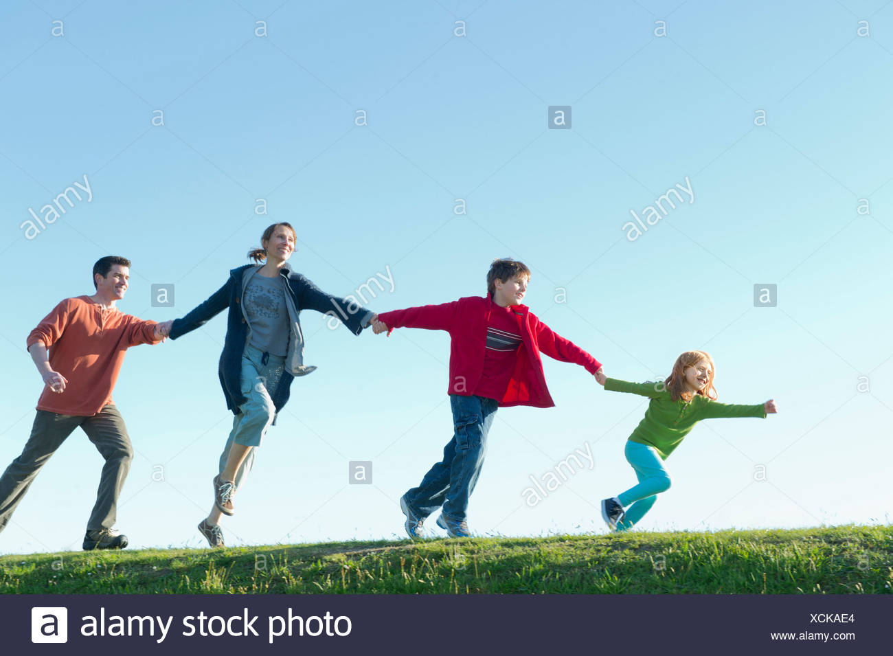 Parents and two children running and holding hands - Stock Image