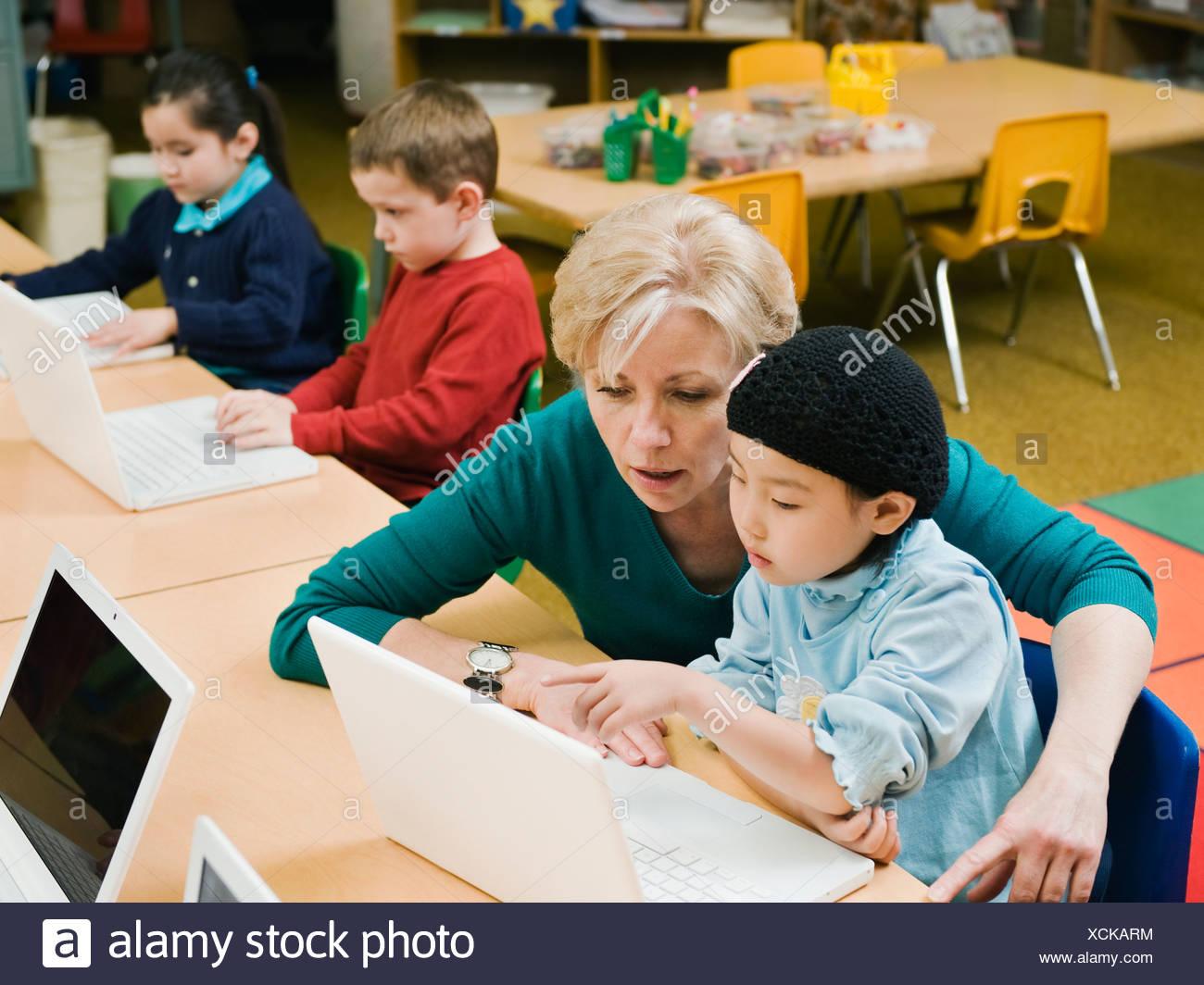 Teacher and kindergarten student looking at laptop - Stock Image
