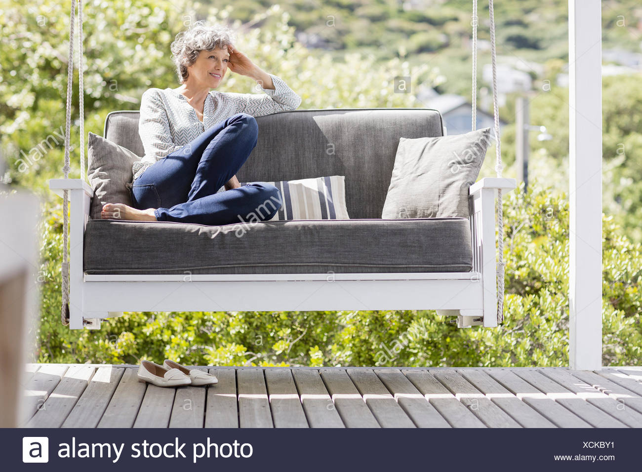 Happy mature woman sitting on a swing in a porch - Stock Image