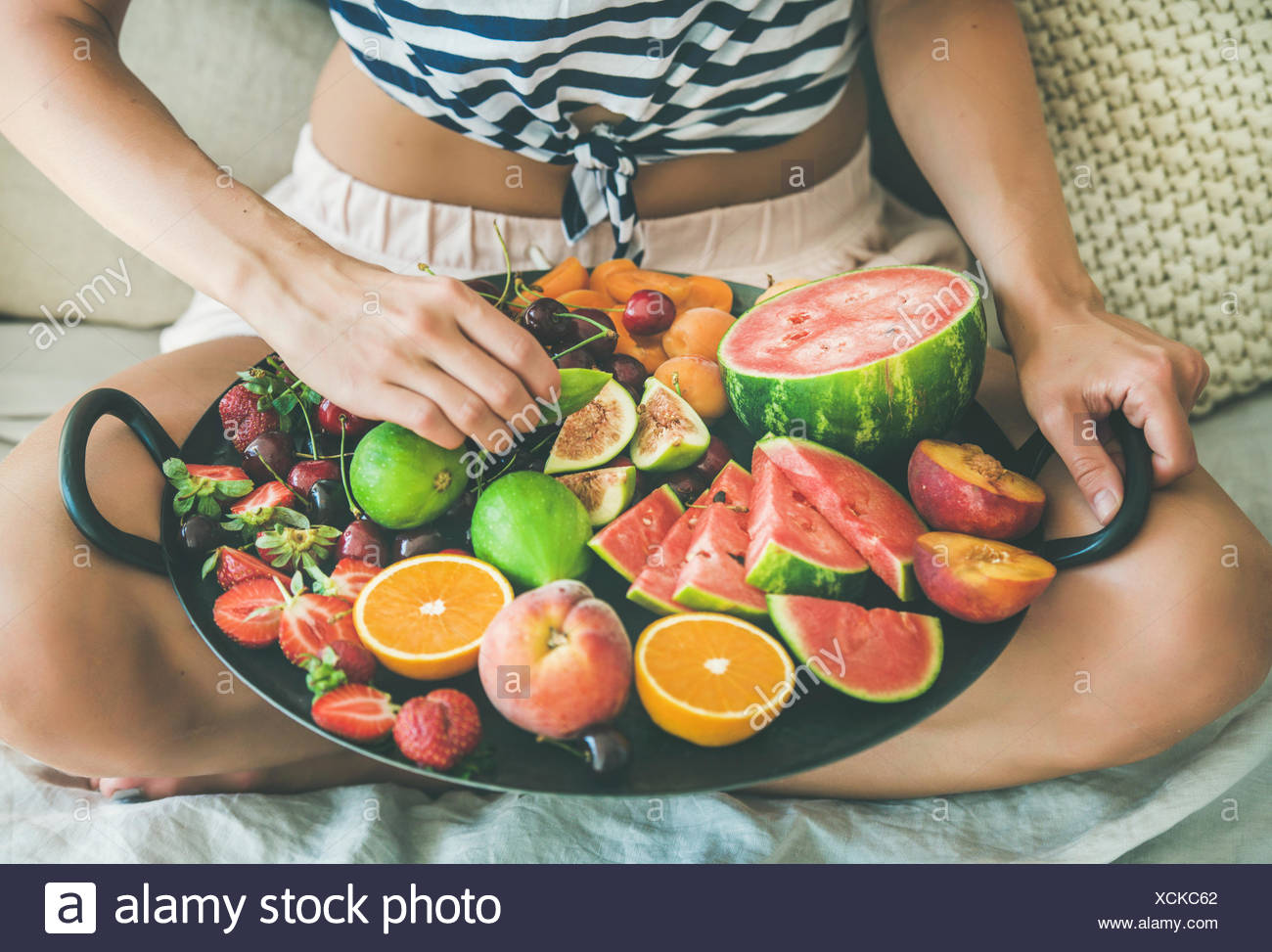 Summer healthy raw vegan clean eating breakfast in bed concept. Young girl wearing striped home shirt sitting and taking fruit from tray full of fresh - Stock Image