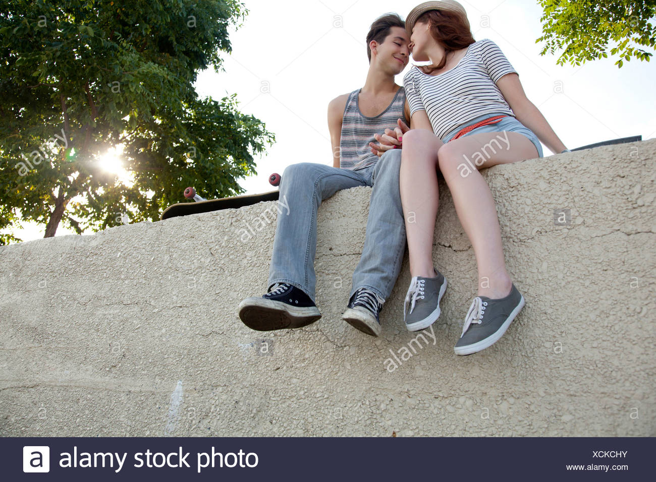 Young couple sitting on wall holding hands Stock Photo