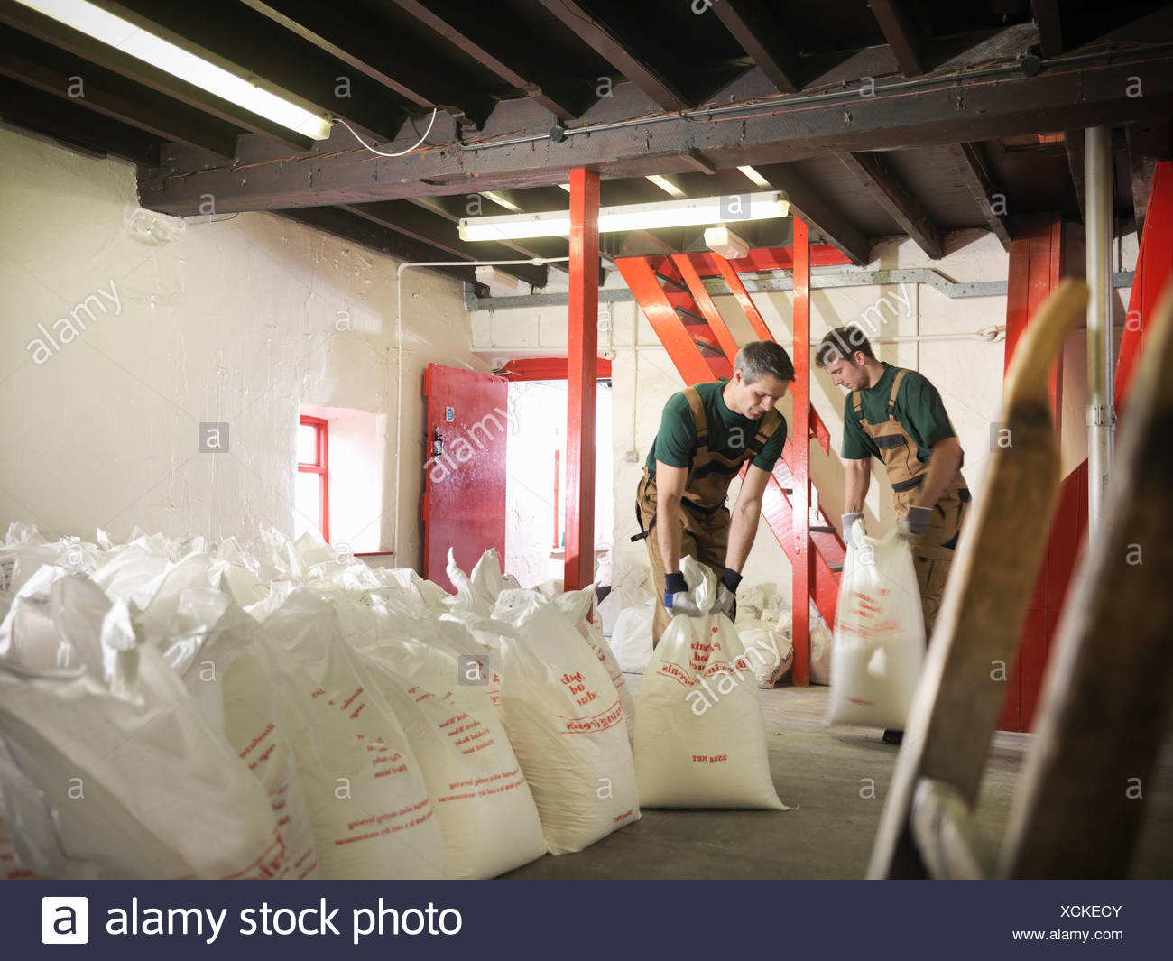 Workers with sacks of grain in brewery - Stock Image