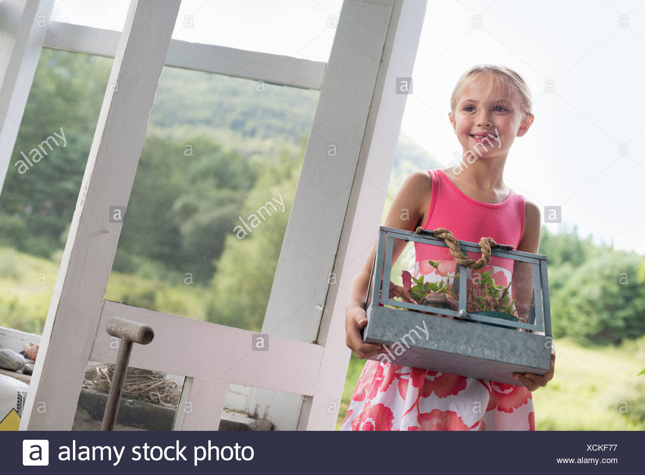 A young girl in a kitchen wearing a pink dress.  Carrying a terrarium containing small plants. - Stock Image