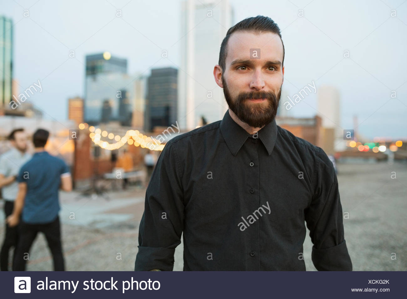 Serious man on urban rooftop - Stock Image