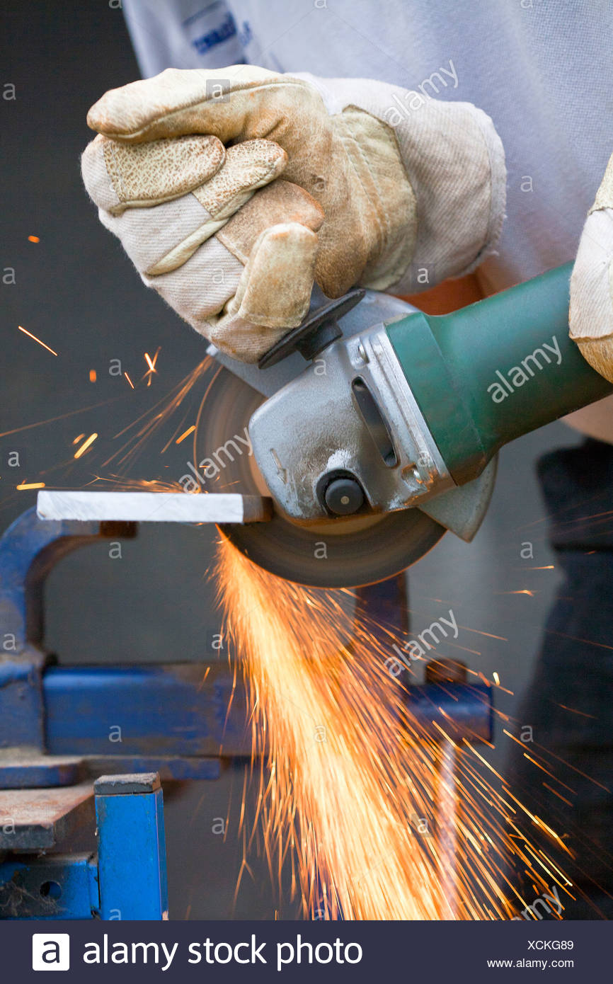 Close up of man cutting piece of iron with angle grinder - Stock Image