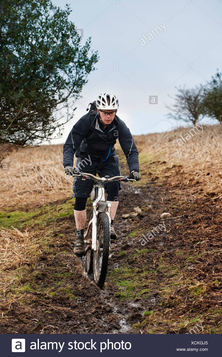 Man riding mountain bike down hill - Stock Image