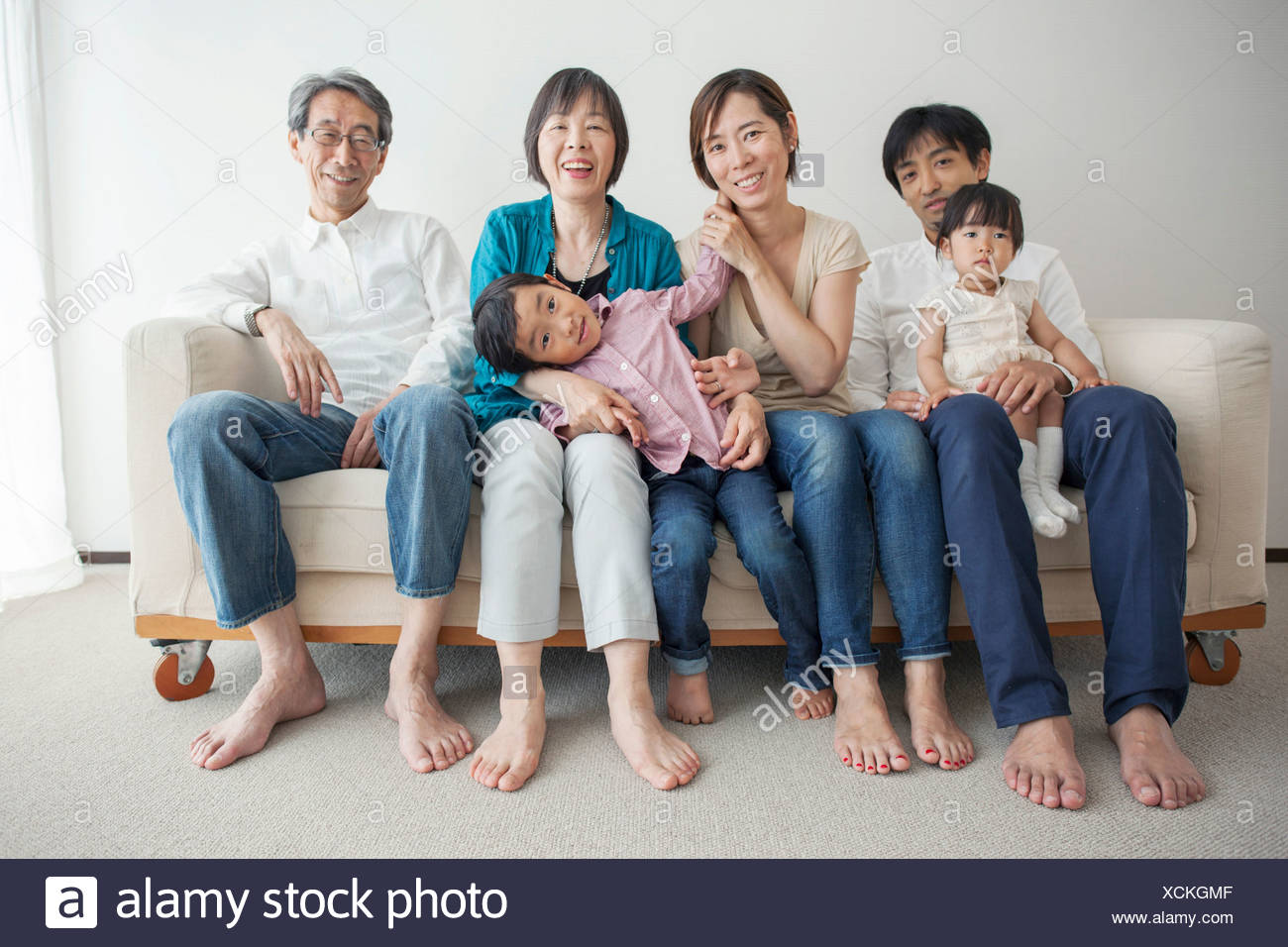 Three generation family sitting on sofa, portrait Stock Photo