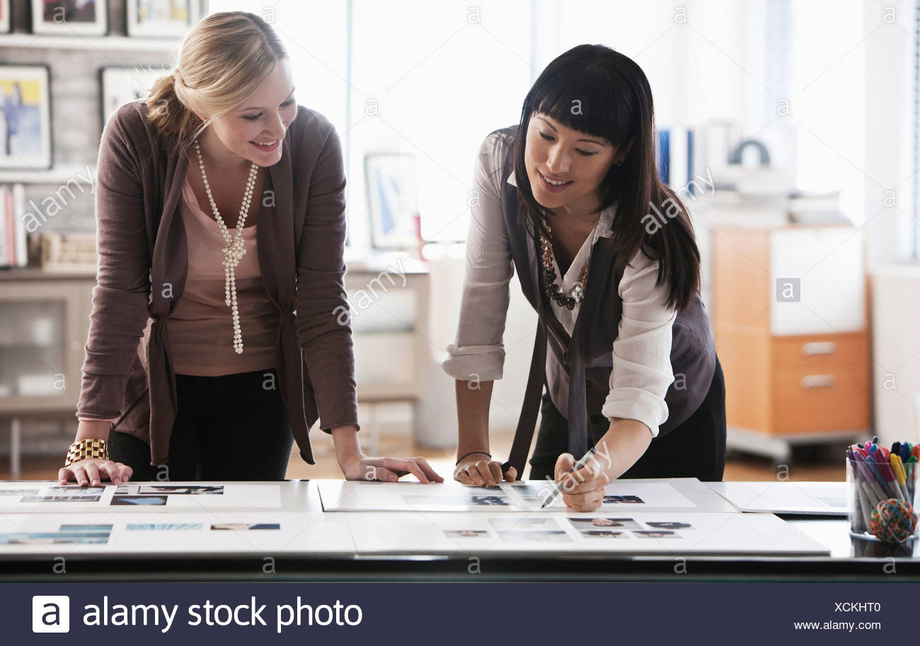 Two creatives studying designs on desk - Stock Image