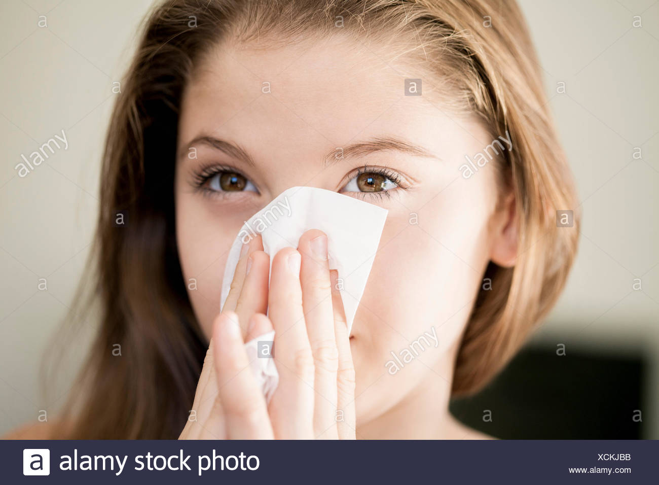Girl wiping her nose with handkerchief - Stock Image