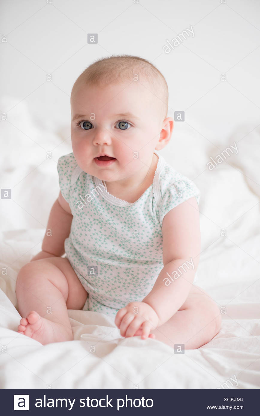 Baby girl (12-17 months) sitting on bed - Stock Image