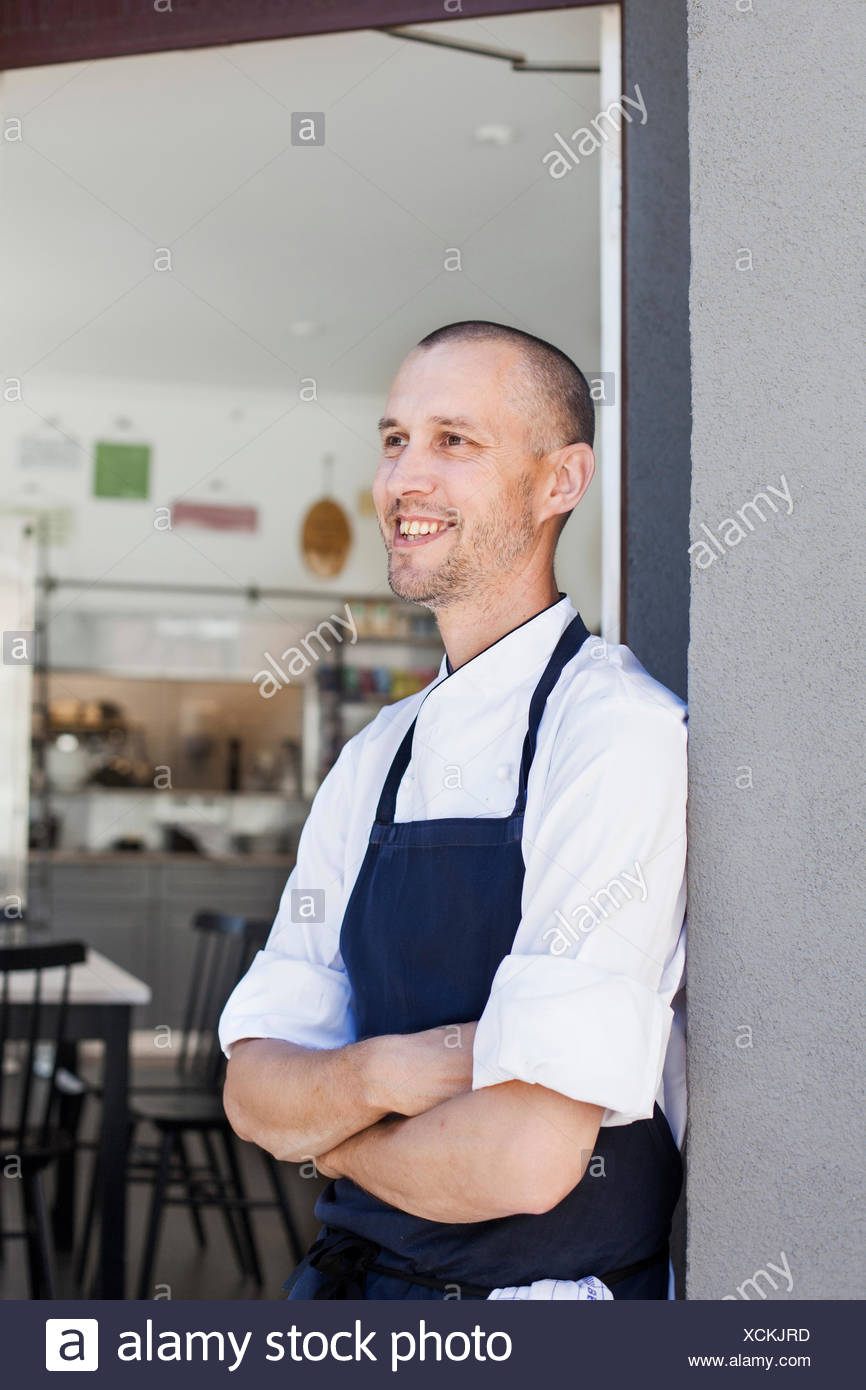 Happy chef standing arms crossed outside commercial kitchen - Stock Image
