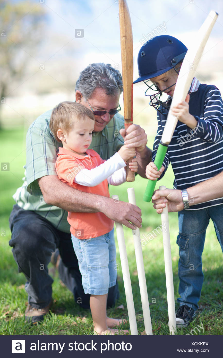 Boys and grandfather preparing stumps for cricket - Stock Image