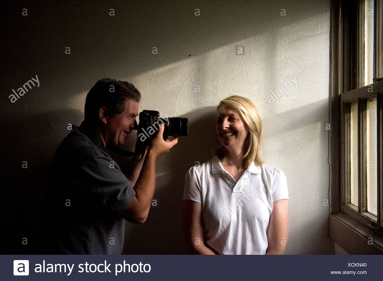 A husband photographs his wife while she laughs. - Stock Image