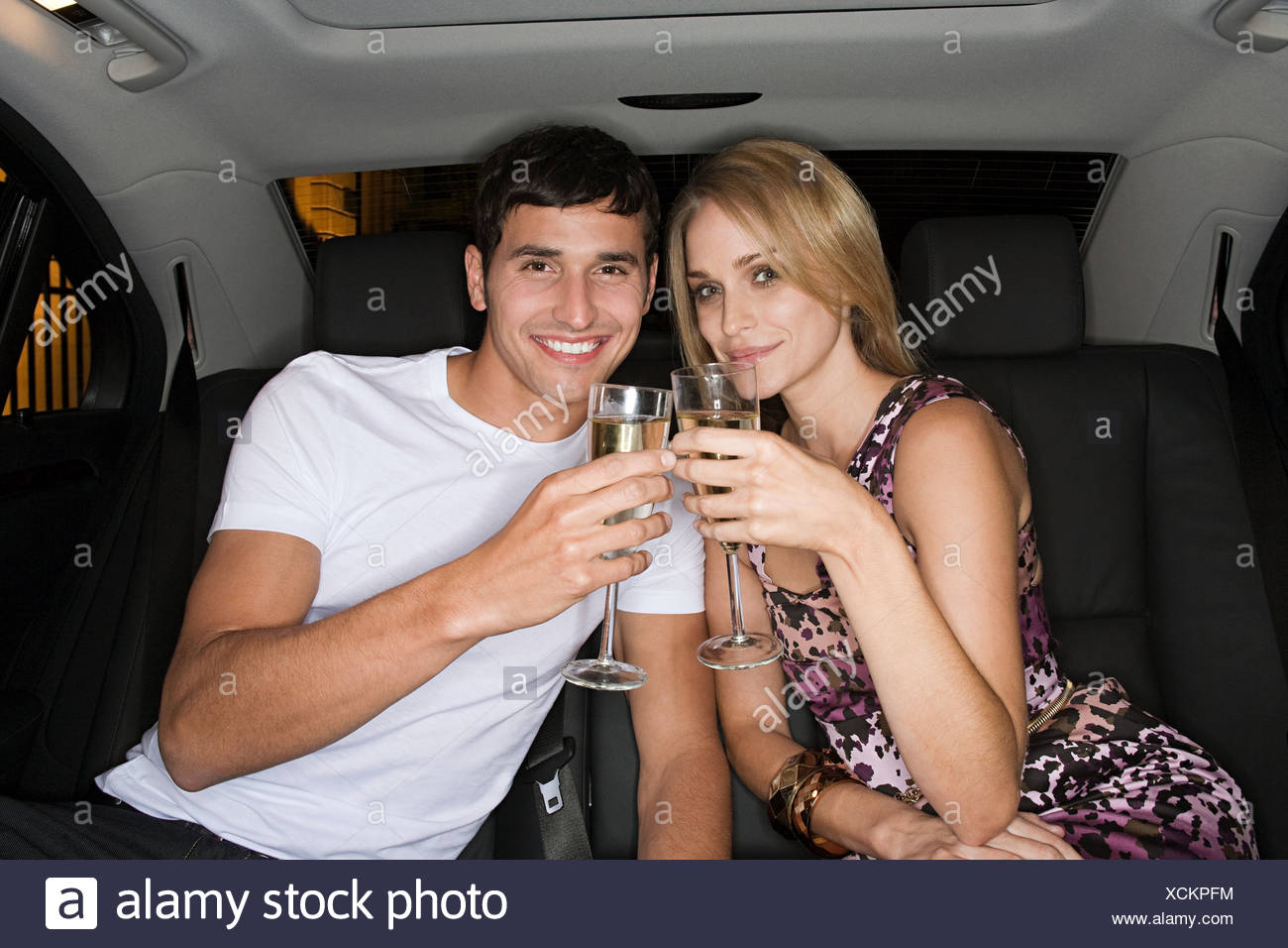 Couple celebrating in the back of a car - Stock Image