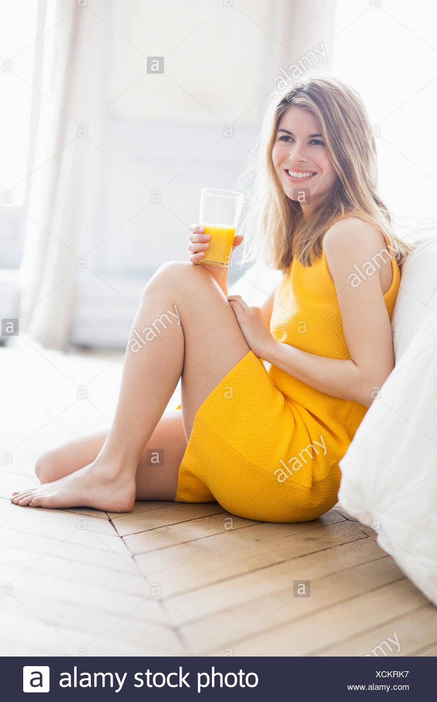 Woman drinking orange juice - Stock Image