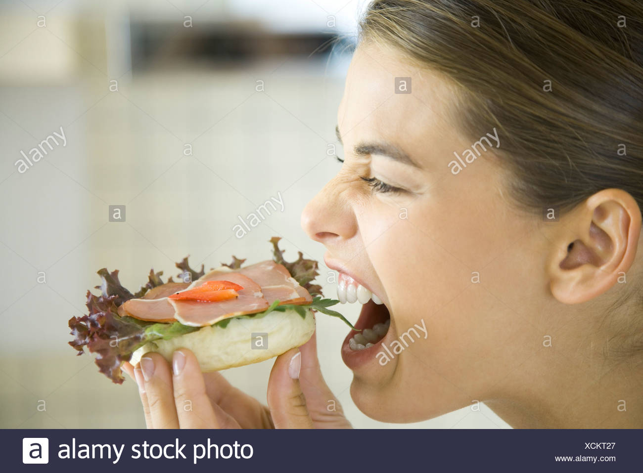 Woman eating open faced ham sandwich, close-up Stock Photo