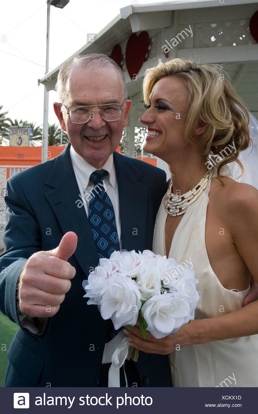 Bride smiling with a senior man giving a thumb's up - Stock Image