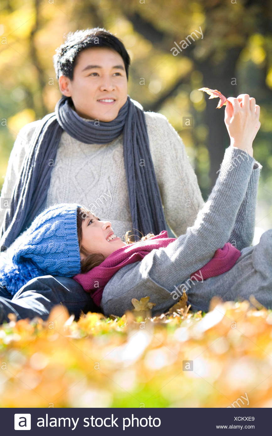 Young Couple in the Park Looking at a Maple Leaf Stock Photo