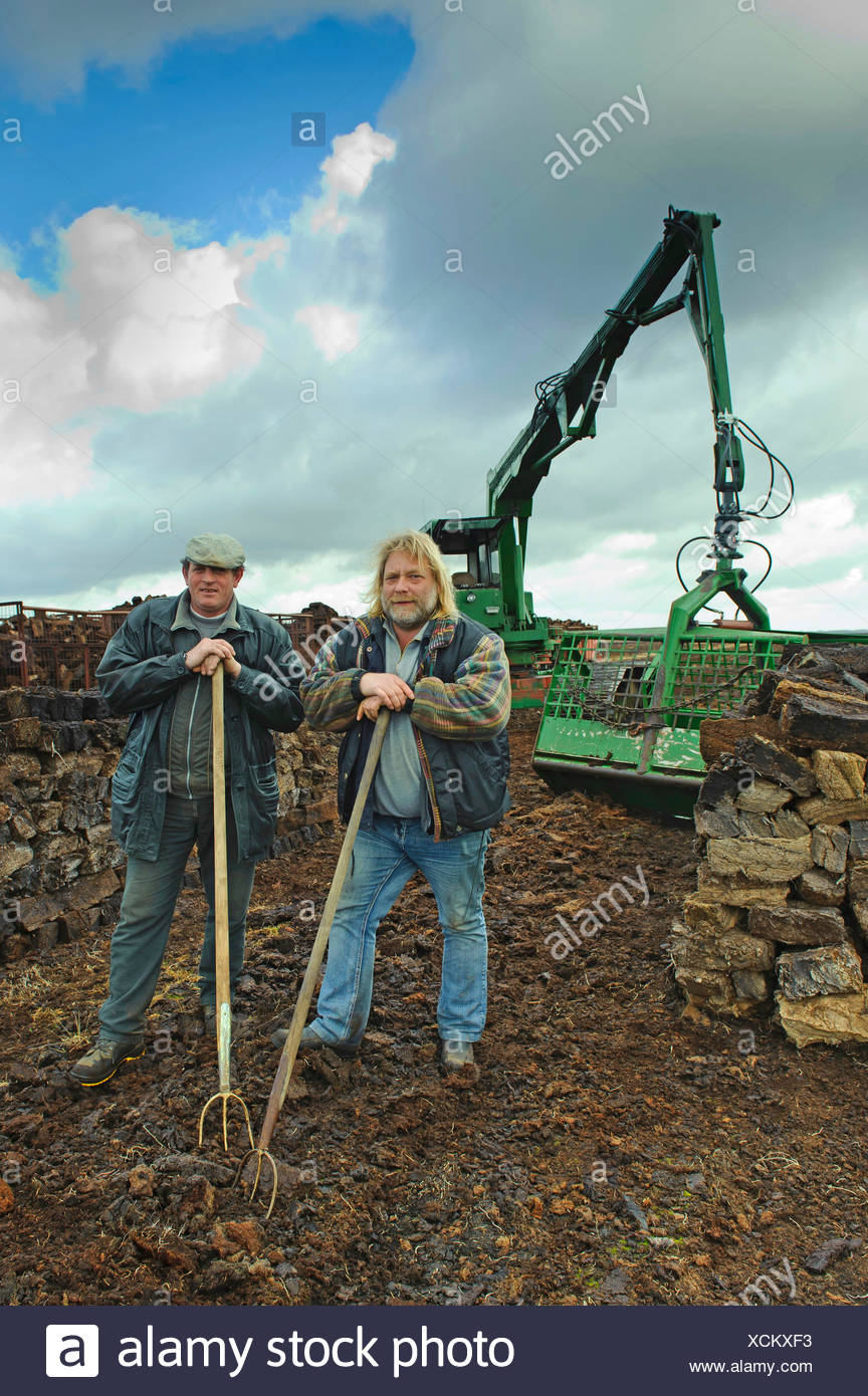 two peat cutters between stacks of bales of peat and the excavator for loading the moor railway, Germany, Lower Saxony, Goldenstedt - Stock Image