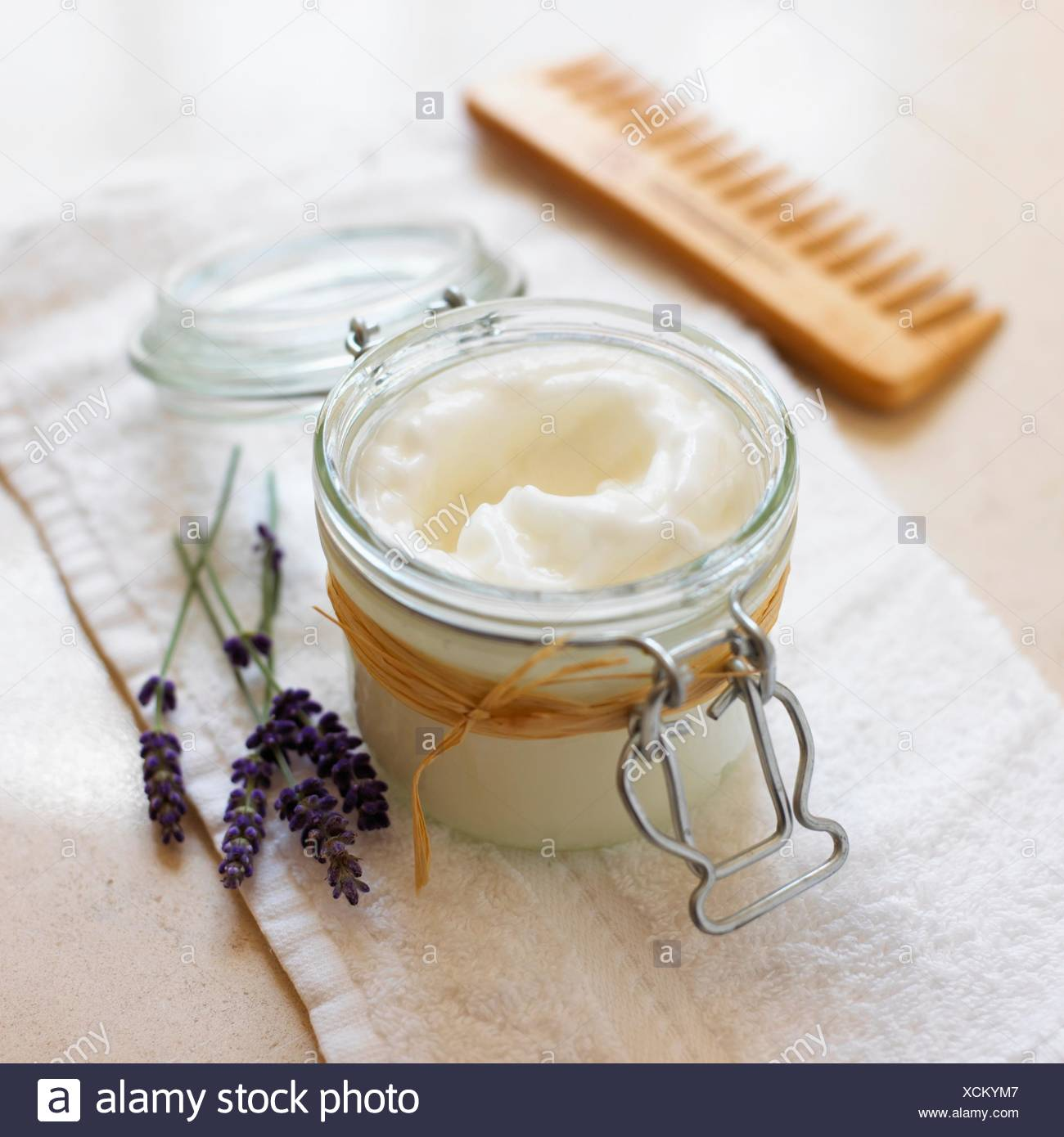 Lavender and rosemary conditioner in a jar, lavender flowers and a comb nearby - Stock Image
