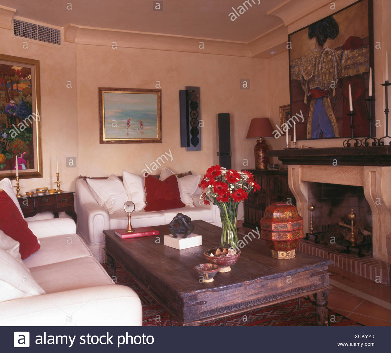 Wooden Indonesian Style Coffee Table And White Sofas In Spanish Country  Living Room With Picture Above Fireplace