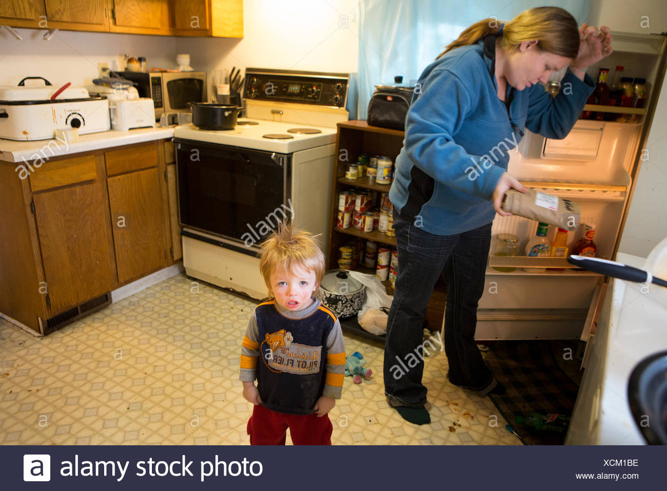 A woman, classified as food insecure, struggles to feed her children. - Stock Image