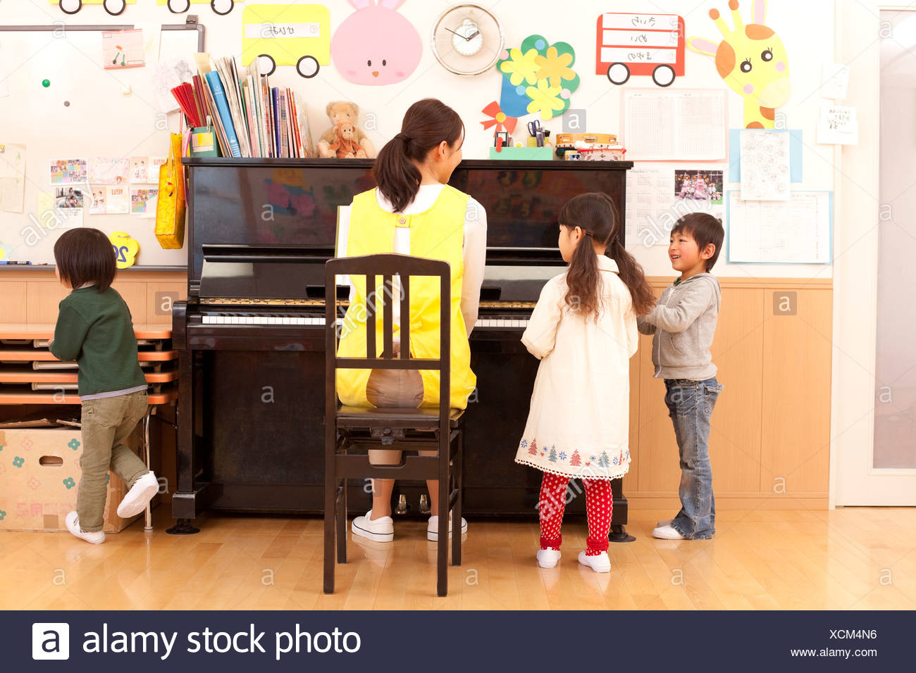 Nursery Teacher Playing Piano with Children Stock Photo