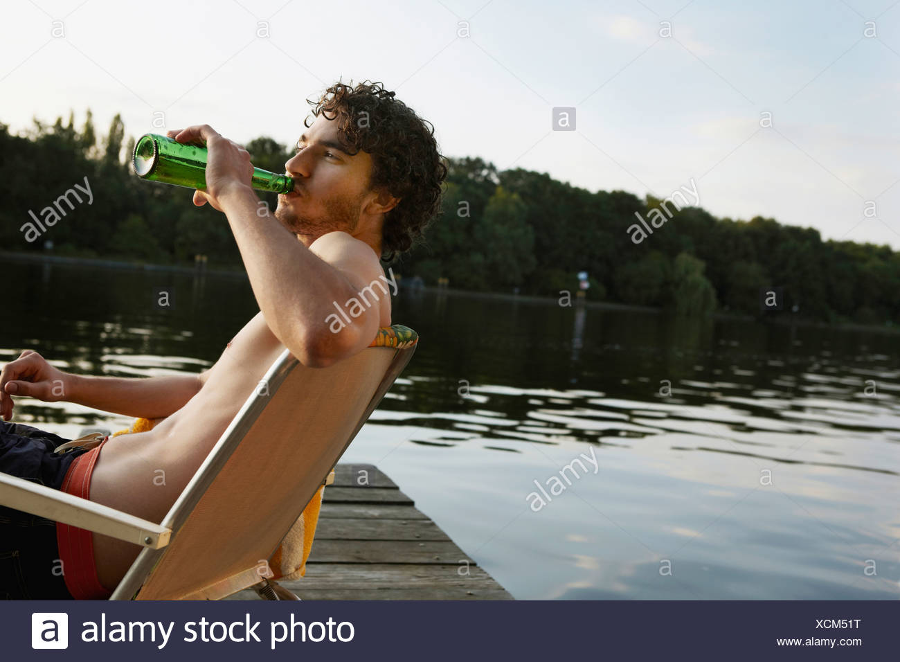 Germany, Berlin, Young man drinking bottled beverage, side view, portrait - Stock Image