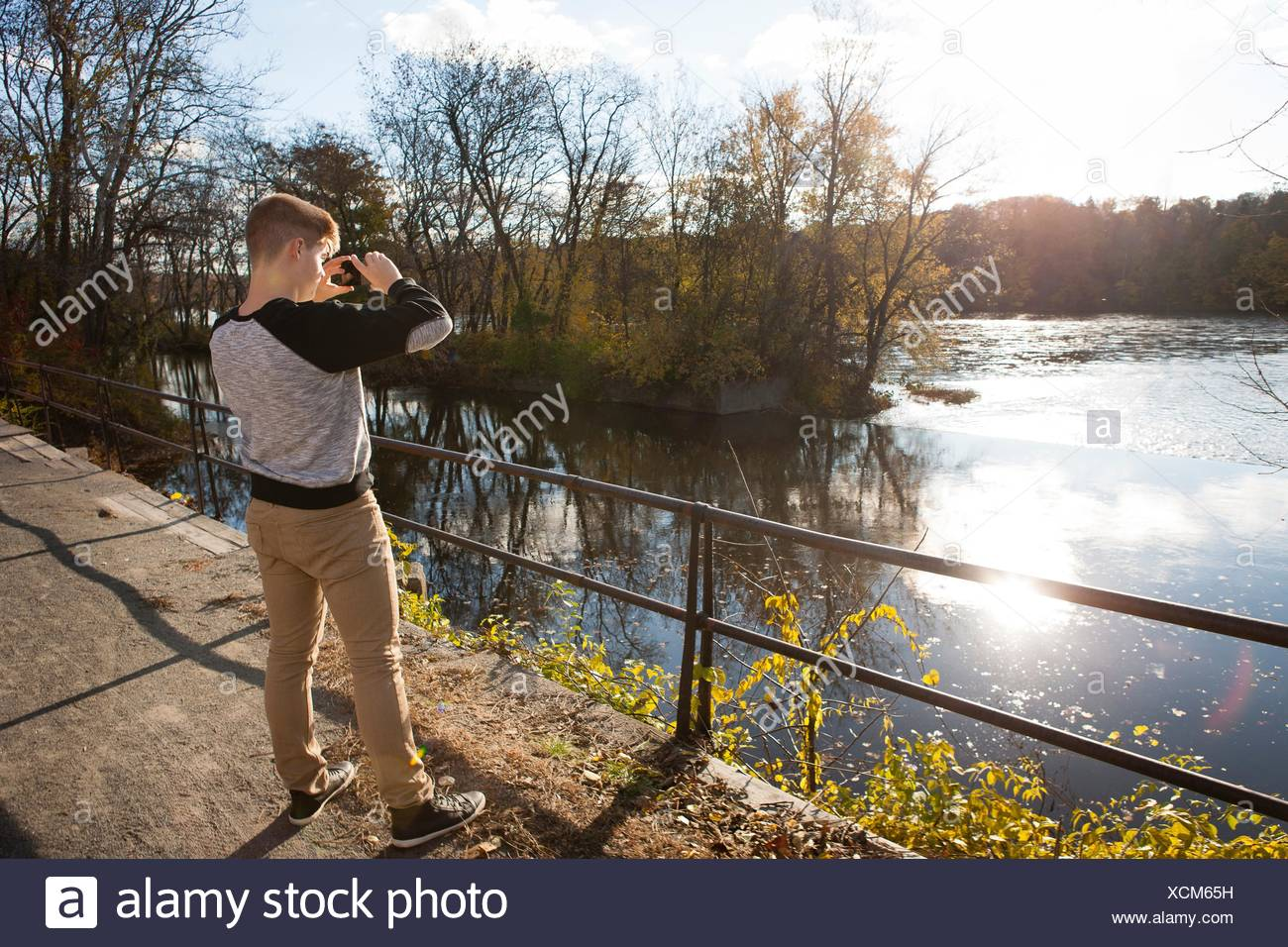 Teenage boy photographing sunlit river in autumn park - Stock Image
