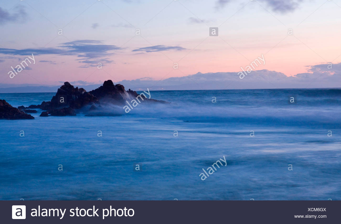 Rocky seashore enveloped in a misty surreal ocean, Monterey Bay at sunset, Central California, USA - Stock Image