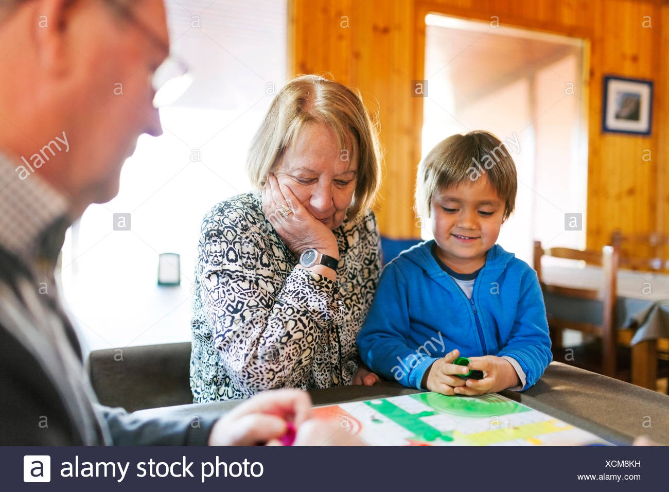 Grandparents playing ludo their grandson Stock Photo