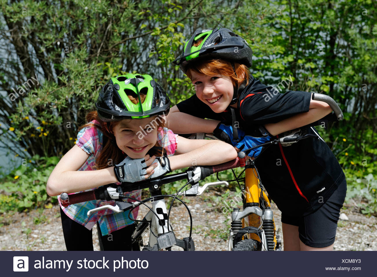 Two children, boy and girl with mountain bikes and helmets - Stock Image