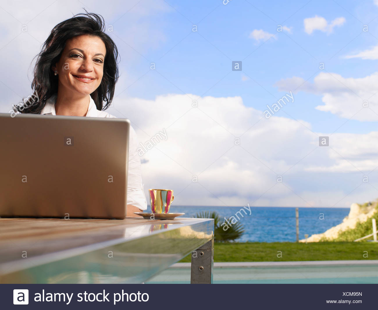 Woman on laptop out doors on decking - Stock Image