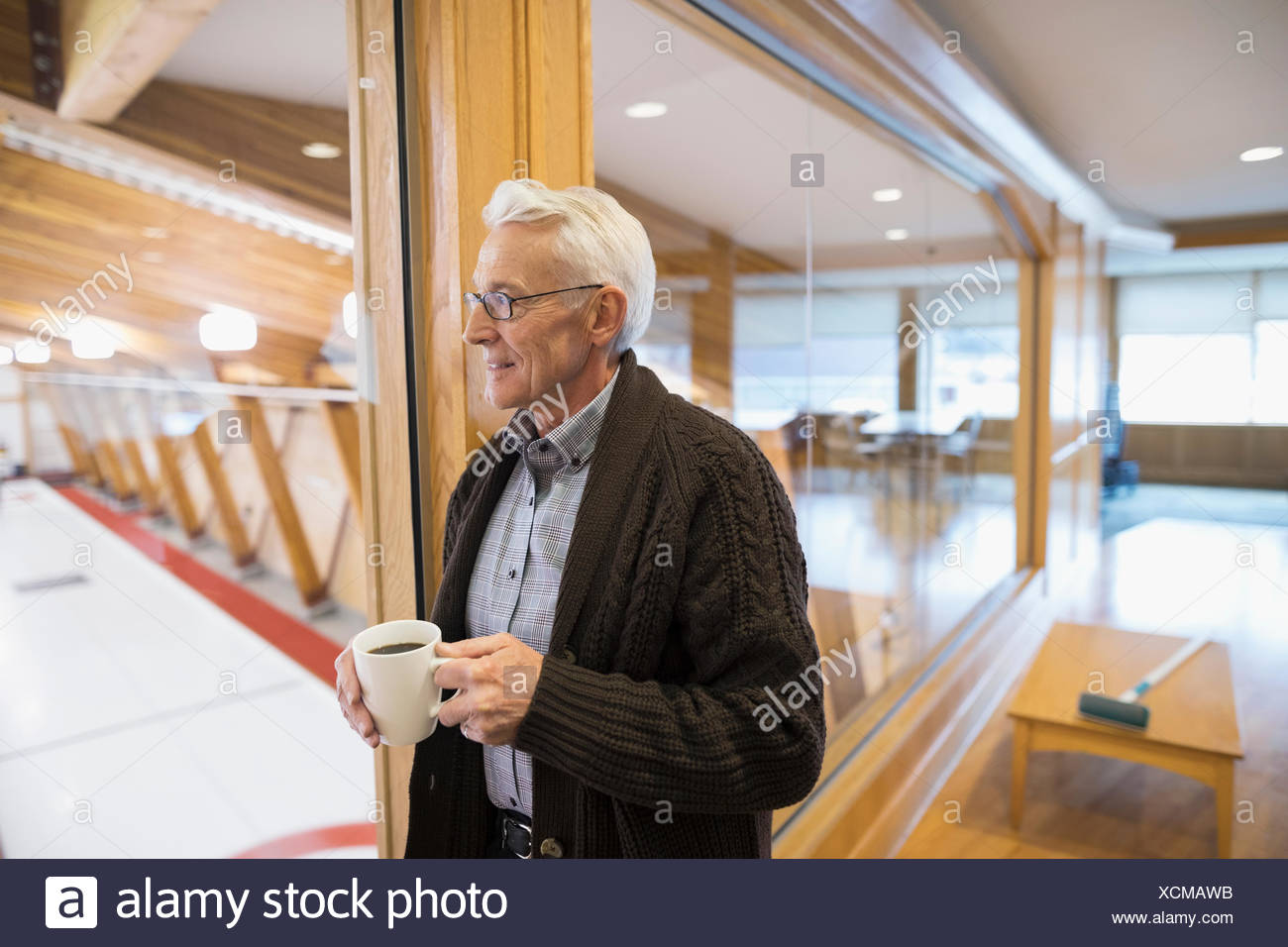 Senior man drinking coffee at curling club - Stock Image
