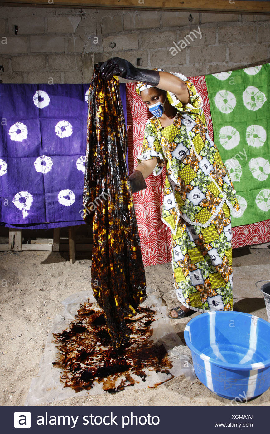 Woman wearing a respirator while batik dyeing fabric, working from home, Maroua, Cameroon, Africa - Stock Image