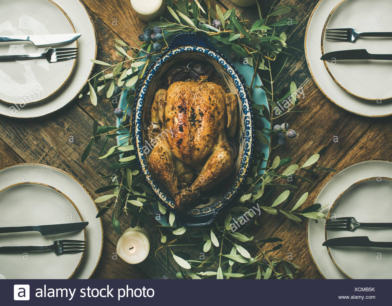 Flat-lay of whole roasted chicken in tray for Christmas eve celebration, plates and candles over rustic wooden background, top view. Holiday table dec - Stock Image