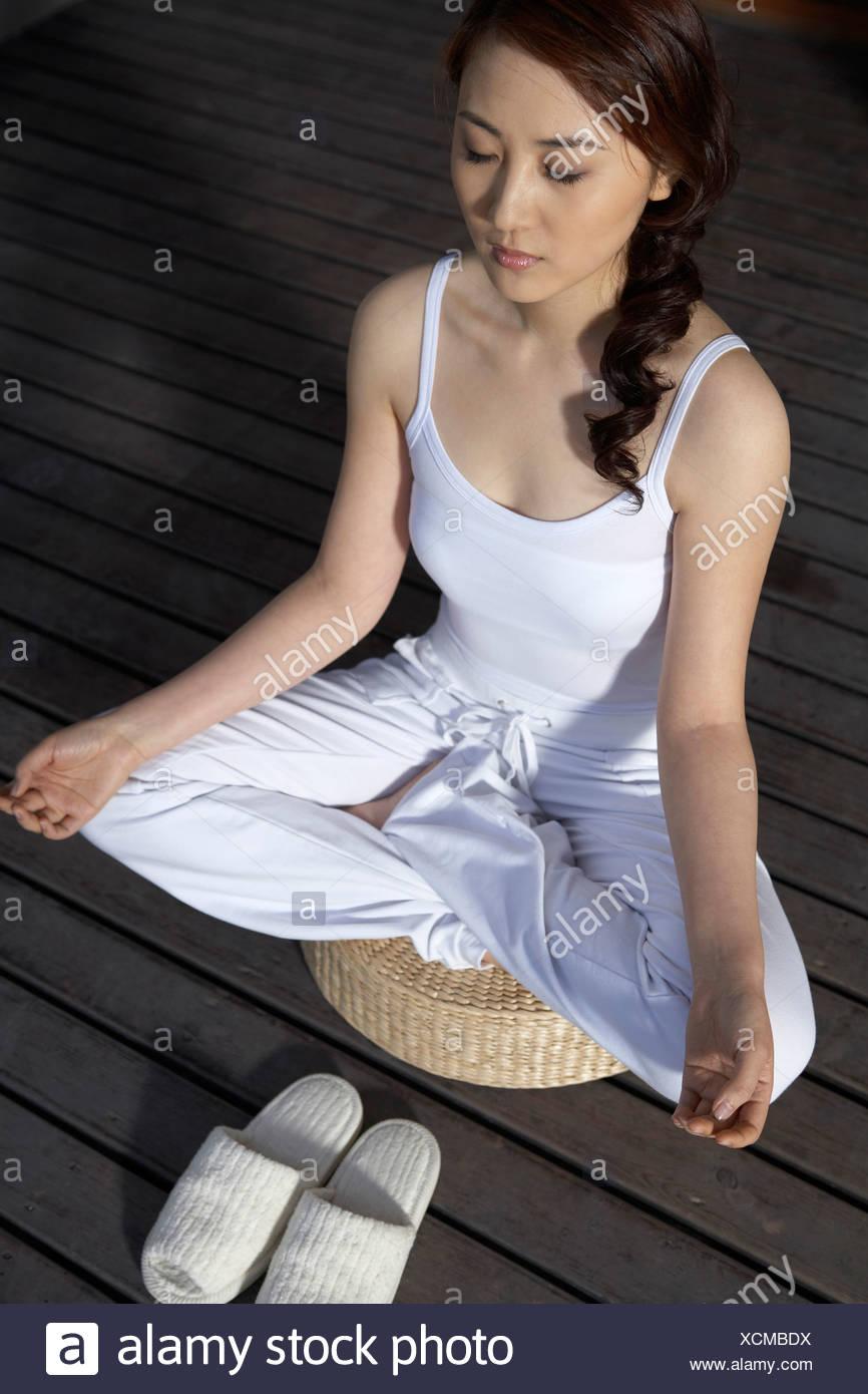 Woman Meditating On Deck Stock Photo