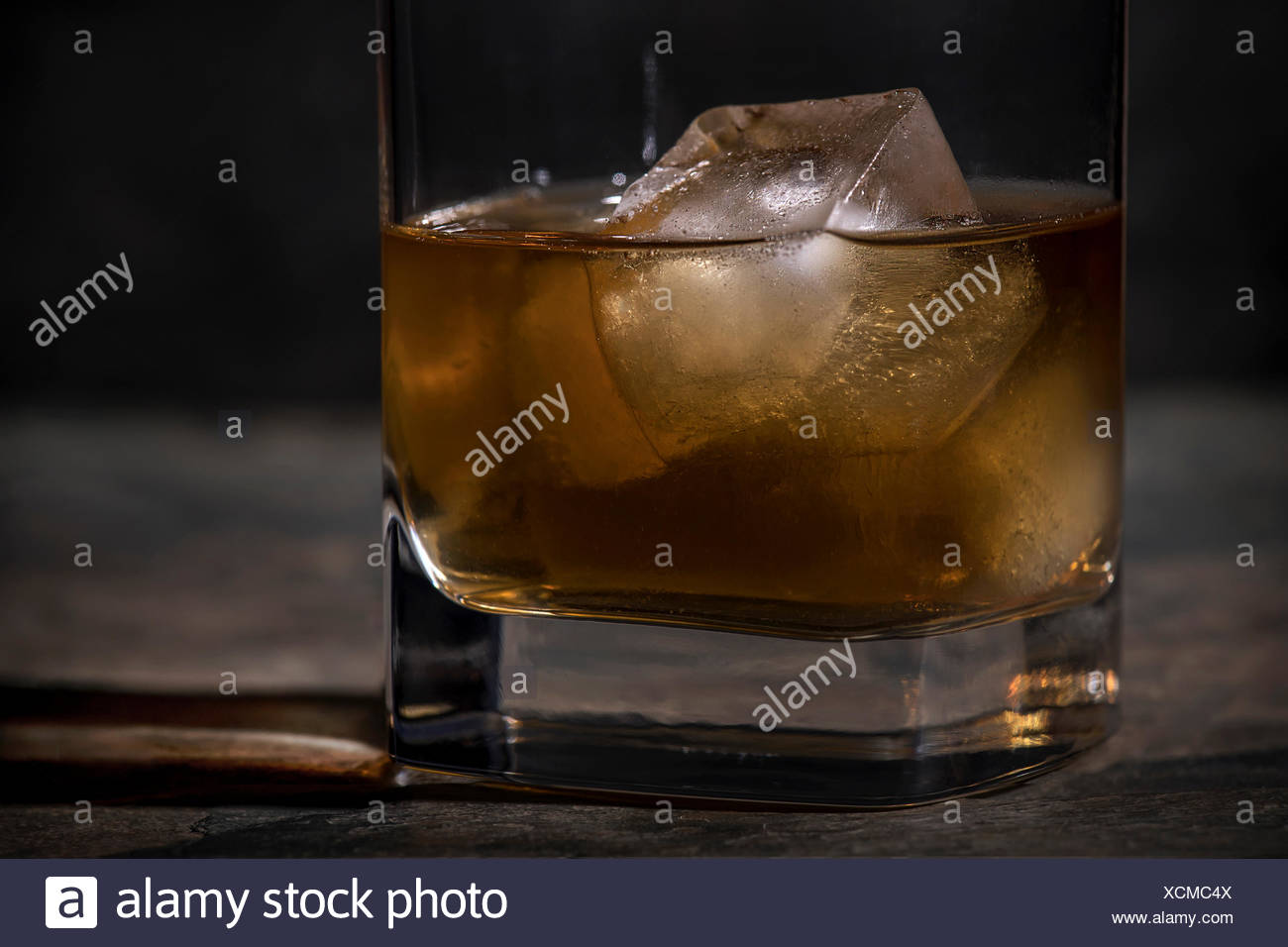 Tight macro shot of a glass of scotch with 1 large ice cube in a low ball glass on a dark stone surface. - Stock Image