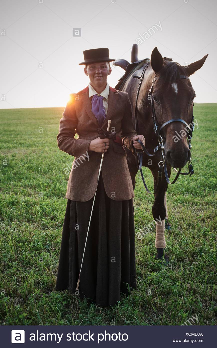 Portrait of woman standing with dressage horse in field Stock Photo