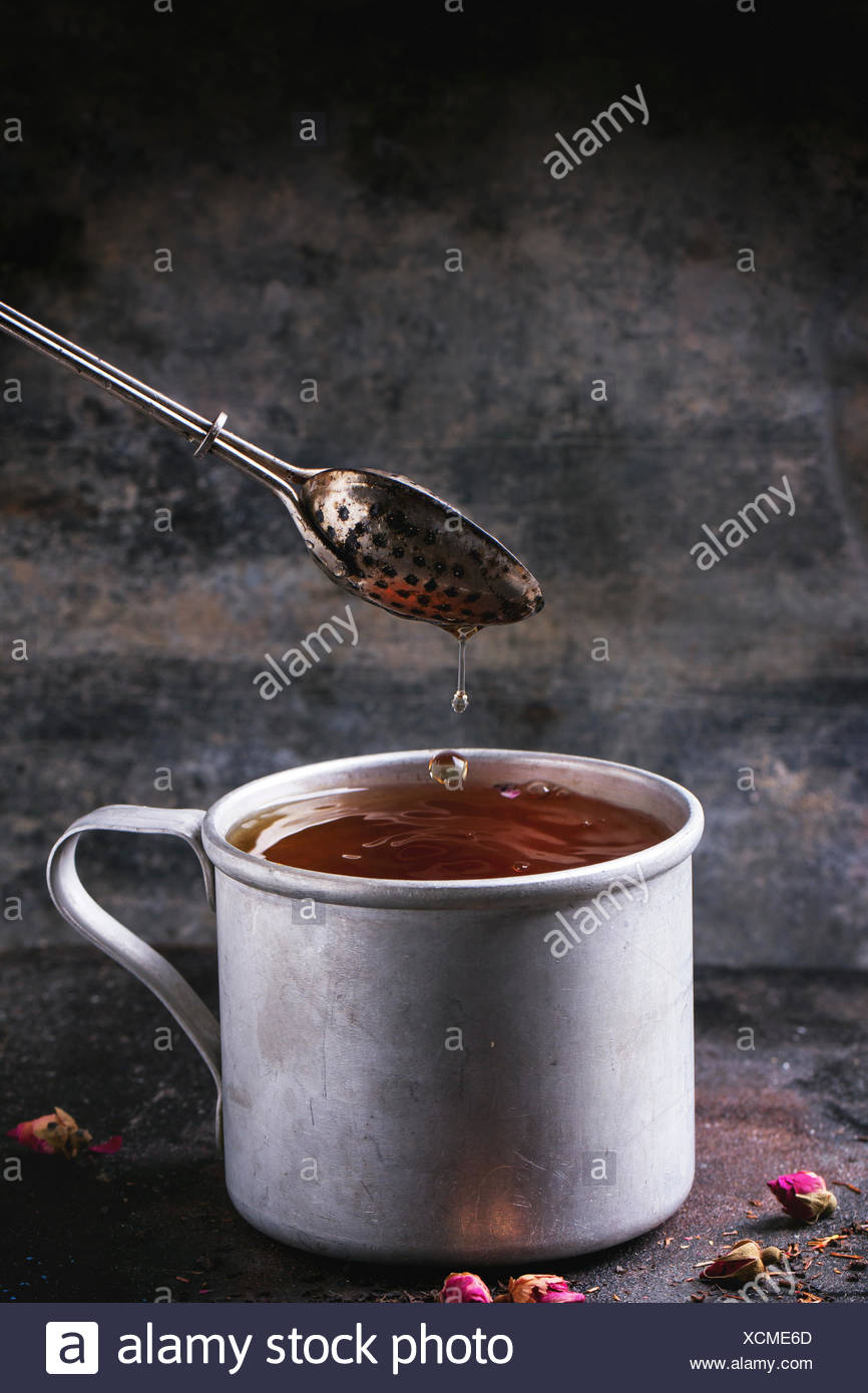 Vintage aluminum mug with flowing hot tea with tea strainer over dark background - Stock Image