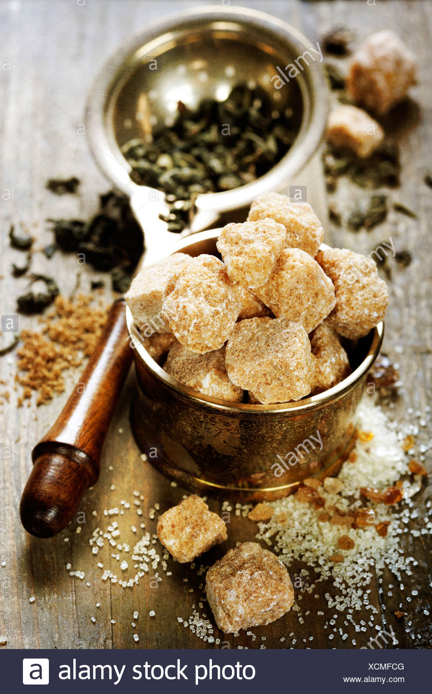 Brown sugar and strainer with tea leafs - Stock Image